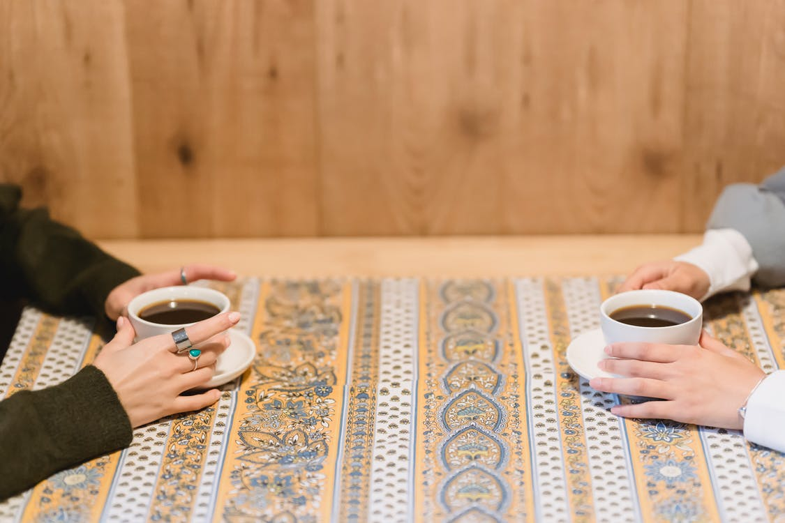Crop faceless women sitting at table with cups of coffee