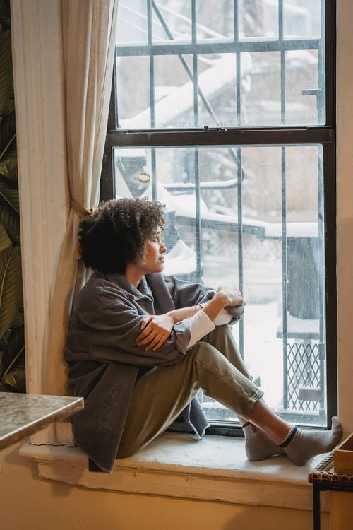 Sad young black woman sitting on windowsill and looking away pensively