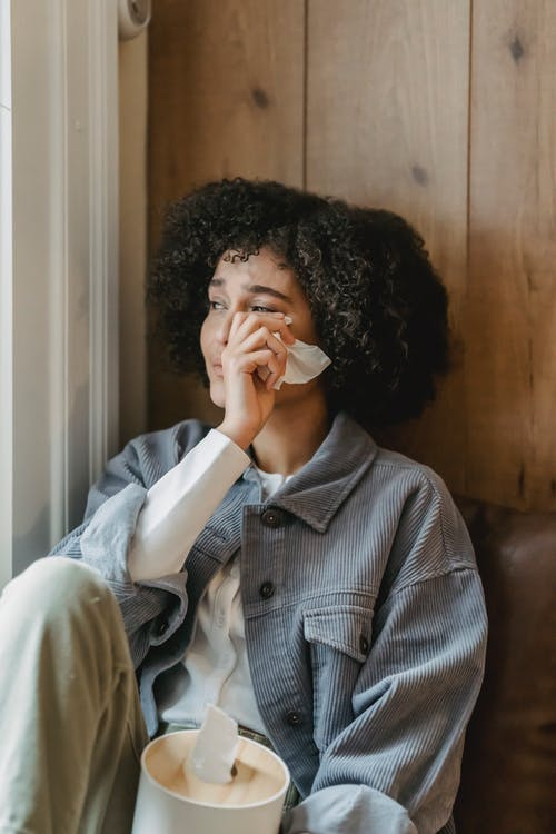 Unhappy young ethnic woman with Afro hair in casual clothes wiping tears with tissue while sitting near window and crying