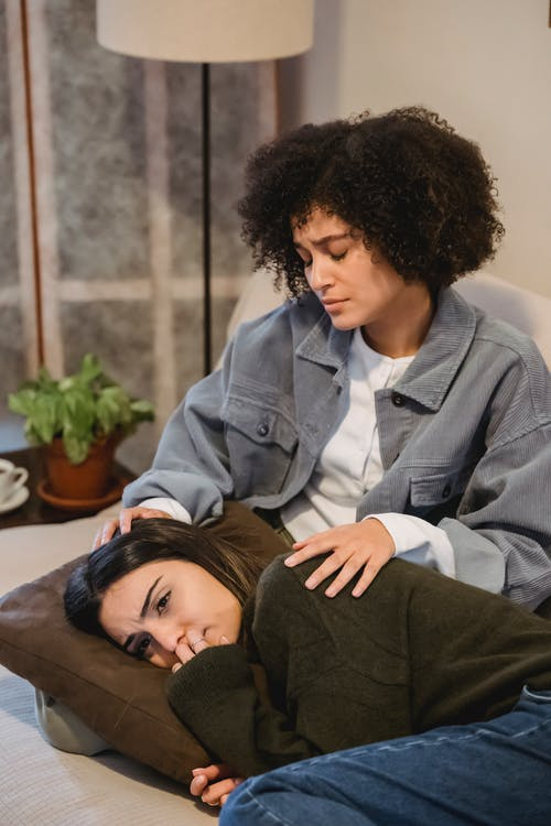 Young melancholic woman lying on couch near black female friend