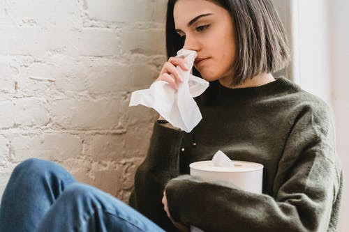 Crop young sad female with dark hair in sweater with tissue in hand crying and looking away sitting near white brick wall at home
