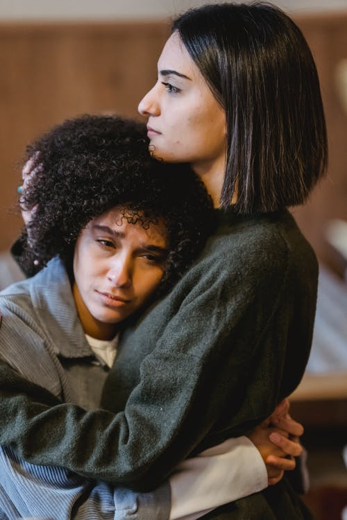 Side view of young lady with dark hair in casual clothes embracing and supporting sorrowful African American female friend at home