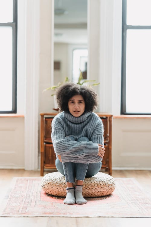 Full body of sad young ethnic woman in casual outfit crying while sitting on pouf near windows and mirror near cabinet in light apartment and looking at camera