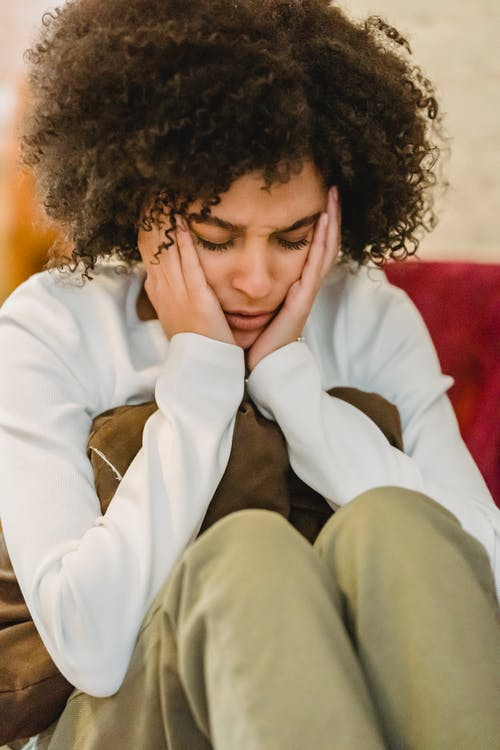 Young sad ethnic lady in casual outfit sitting with pillow with hands on head and closed eyes in light room