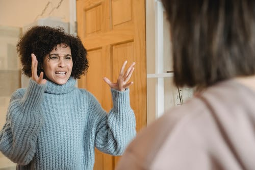 Angry young multiracial ladies in casual clothes standing in bright apartment near door while having disagreement and looking at each other