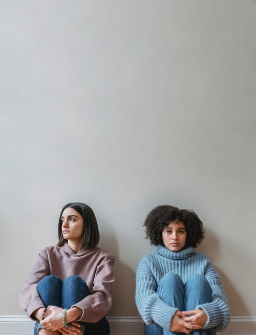 Sad multiracial girlfriends sitting together near wall in room