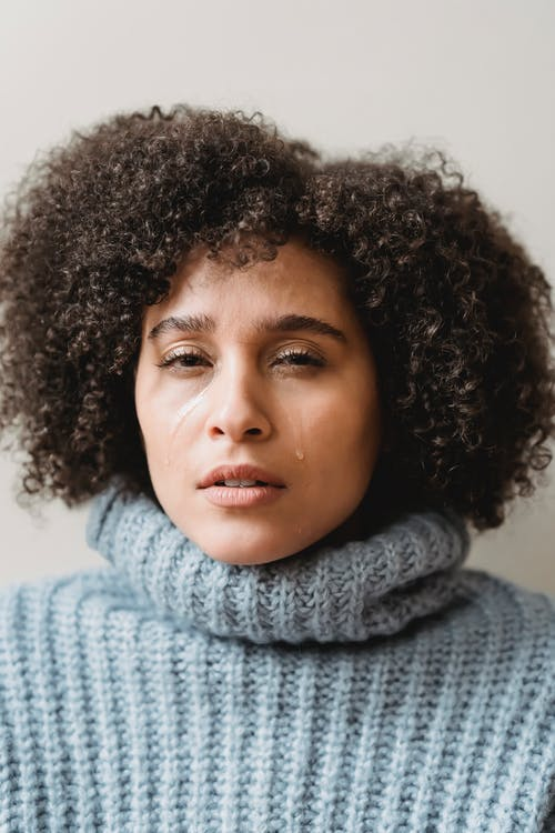 Crying ethnic woman with dark curly hair