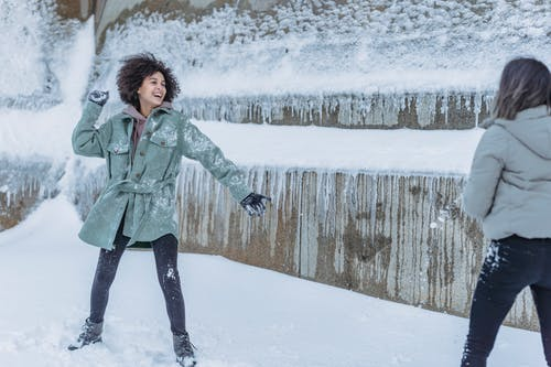 Laughing female friends in warm clothes standing near stone wall covered with snow and playing snowballs in winter