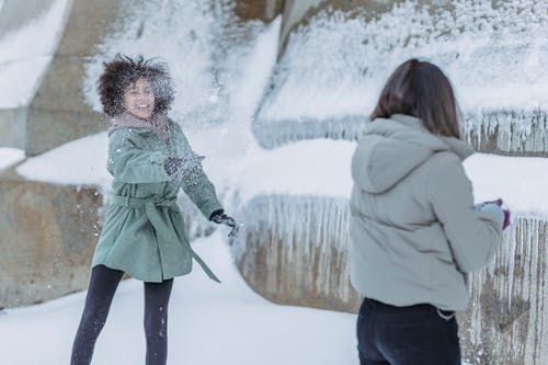 Young women in warm clothes playing snowballs
