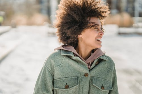 Laughing ethnic woman with dark curly hair in warm outerwear looking away while strolling outdoors in wintertime