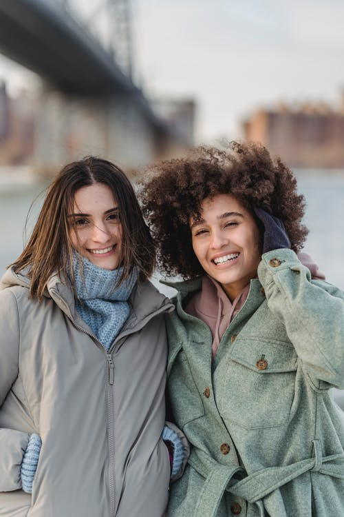 Smiling diverse female friends in warm clothes looking at camera while standing on city embankment on blurred background