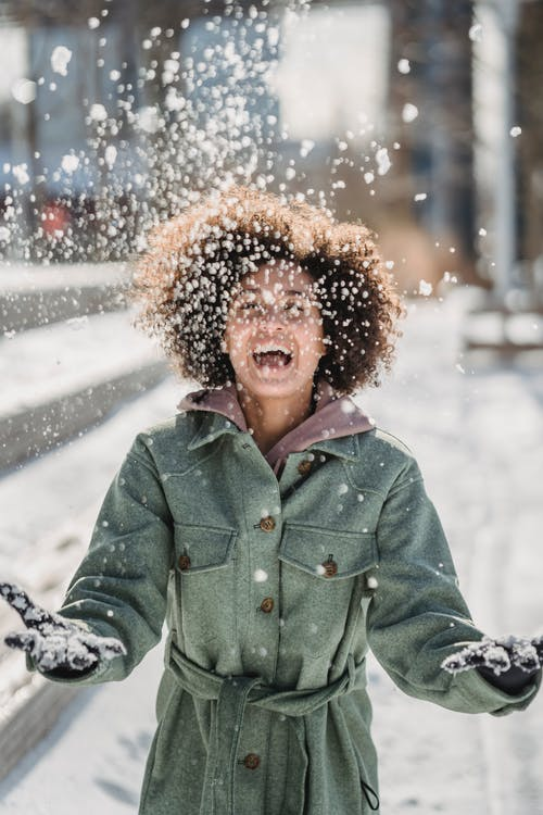Young ethnic female in warm clothes with curly hair laughing while tossing up snow on blurred background in city