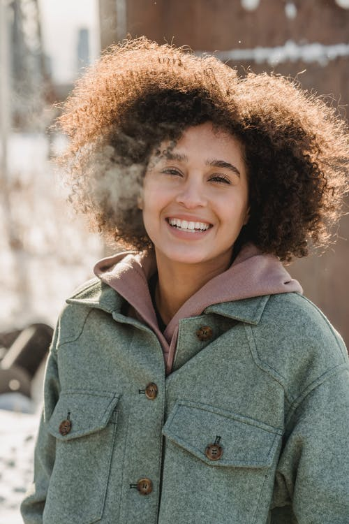 Happy ethnic female with curly hair wearing warm clothes looking at camera while standing on sunny street on blurred background