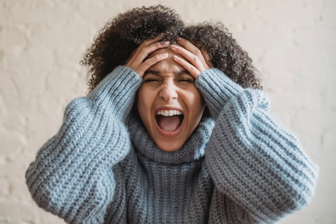 Upset ethnic woman screaming in room
