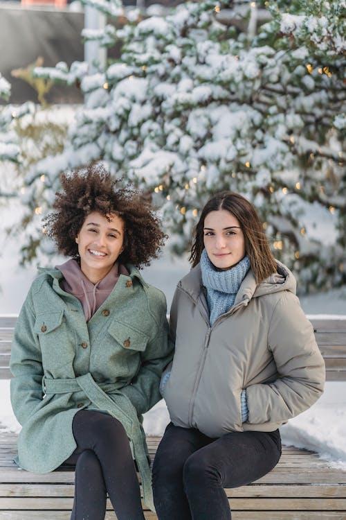 Frau Im Grünen Mantel, Der Auf Schneebedecktem Boden Sitzt