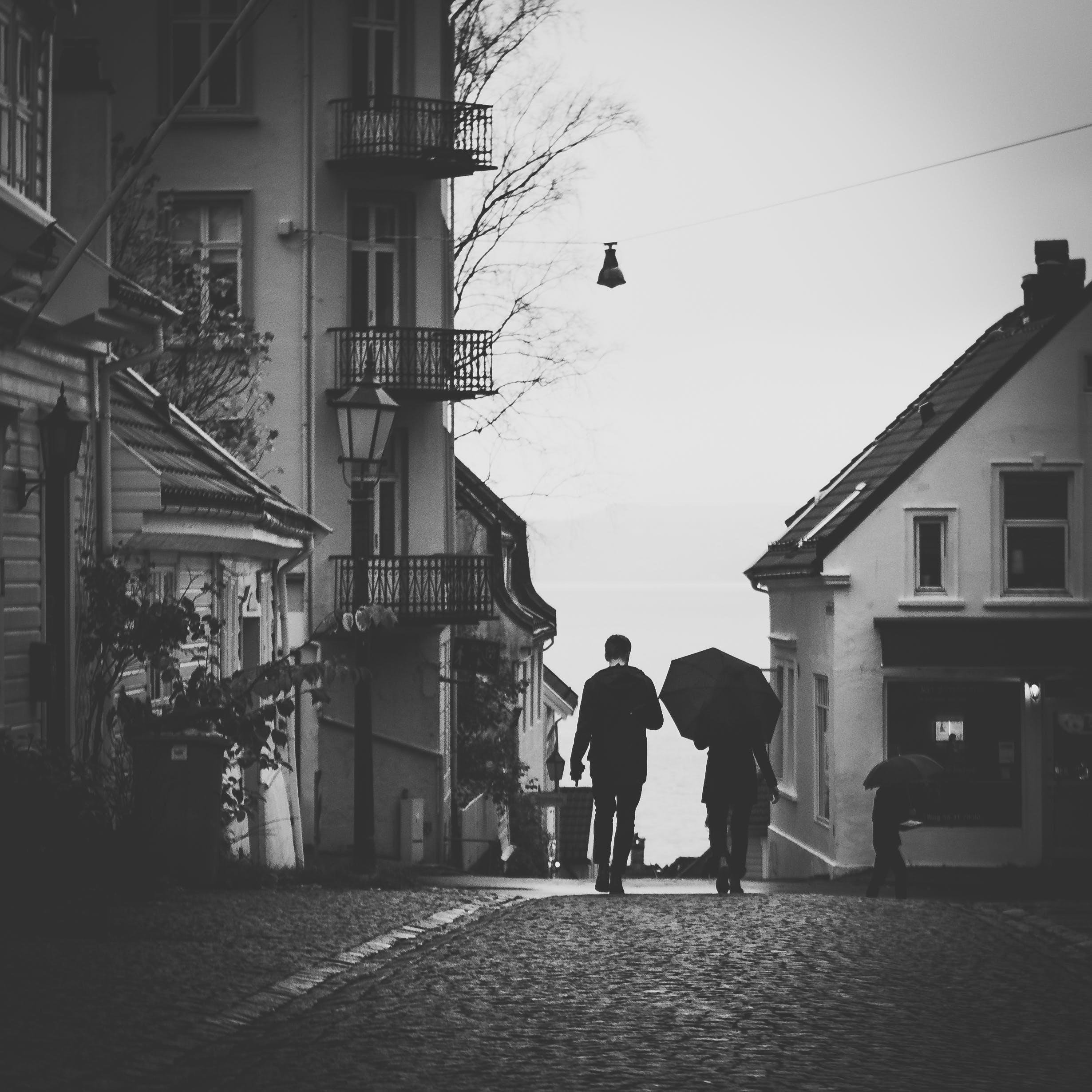 Grayscale Photo Of Man Beside Woman Under Umbrella Walking On Pavement