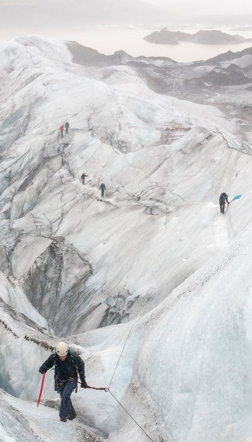 People Hiking the Snow Covered Mountain