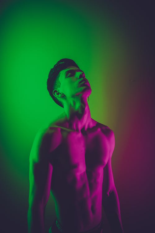 Fit shirtless man standing with eyes closed in neon lights