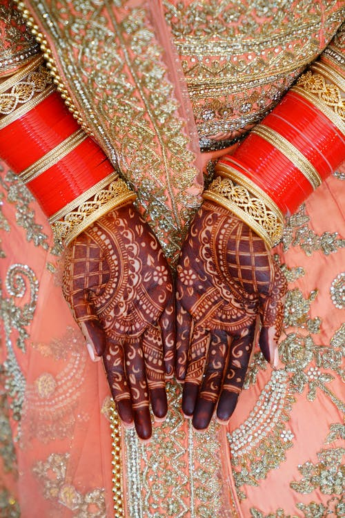Crop Indian bride in traditional sari with henna on hands
