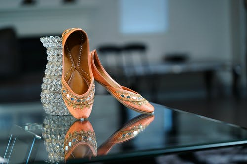Elegant pink ballet flat shoes decorated with sparkling crystals and arranged on glass table near cut glass vase