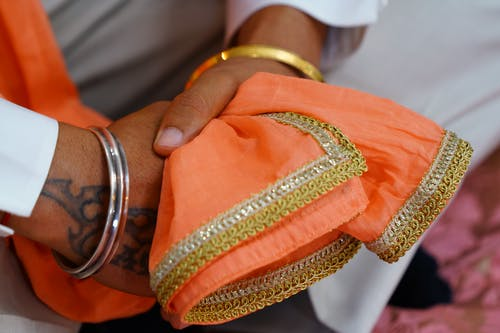 Crop unrecognizable Indian groom wearing traditional white wedding clothes and pink scarf with embroidery sitting with hands clasped