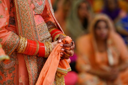 Crop unrecognizable Indian bride in traditional fancy gown
