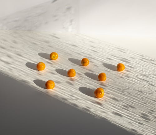 Sweet yellow ripe cherry tomatoes arranged on white surface in shadows in light studio