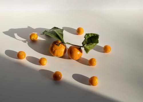 Ripe yellow Physalis fruits and mandarins scattered on white surface
