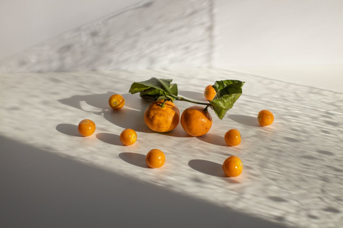 Healthy tangerines and groundcherries scattered on white surface in daylight
