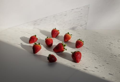 High angle of fresh ripe red strawberries scattered on white table on sunny day