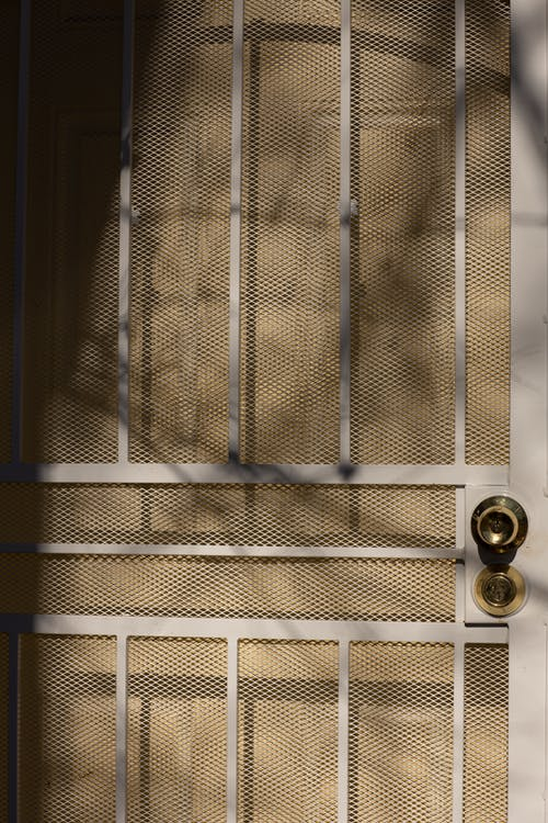 Closed metal grid gate with bars and handle and wooden door of residential house on sunny day