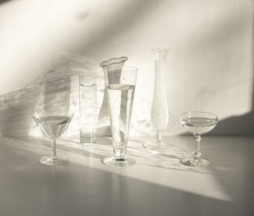 From above set of classic crystal glasses of various shapes with water served on white table in sunlight