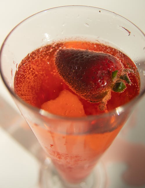 High angle of glass of refreshing fizzy soda drink with strawberry served on white table
