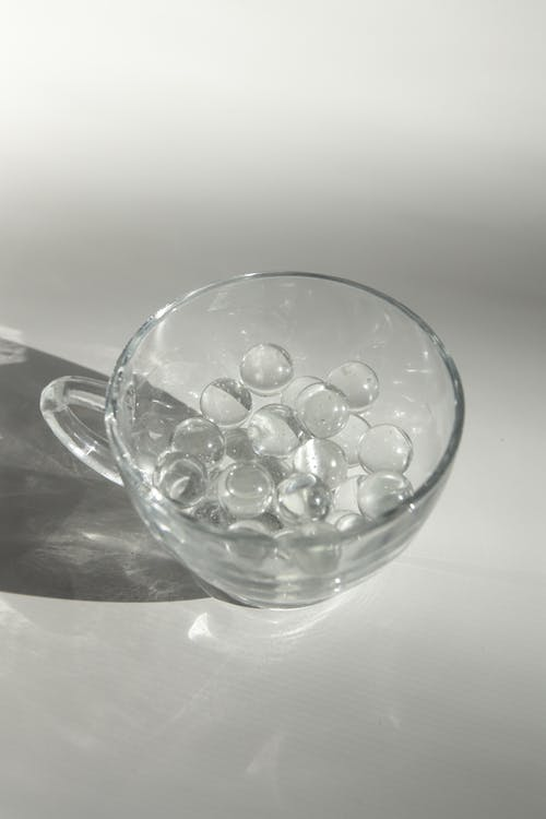 Glass cup with small transparent balls on white surface