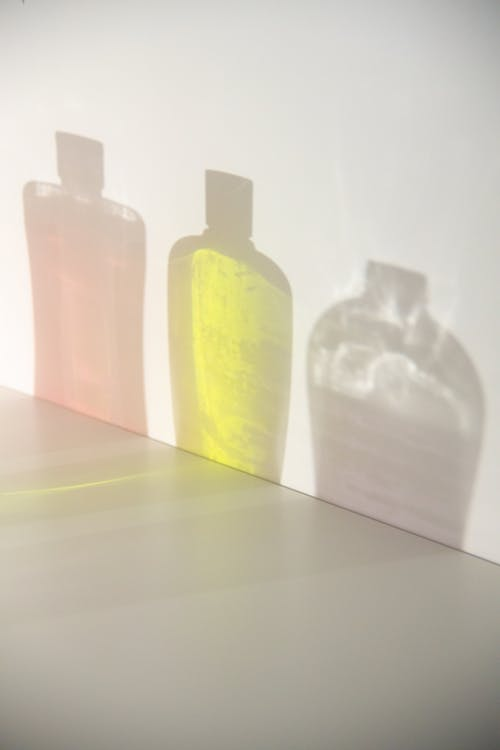 Assorted bottles of shampoos reflecting on wall