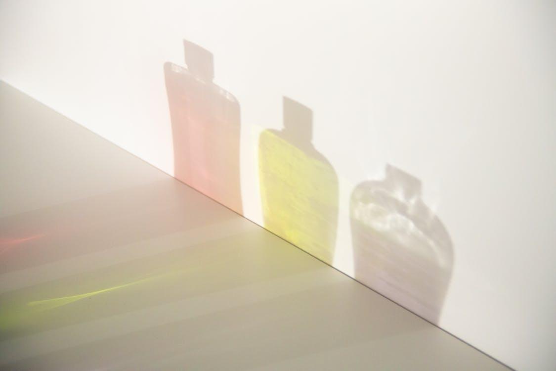 棕色的木桌上的綠色和黃色玻璃瓶