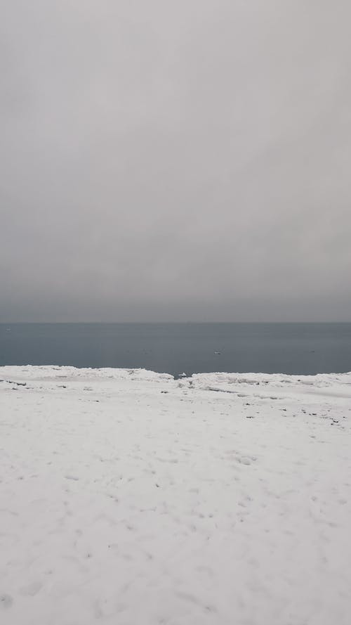 Scenery view of snowy coast against endless ocean with horizon line under gray sky in winter