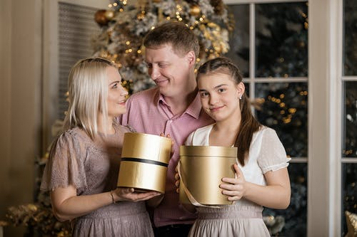 A Family Standing Near the Christmas Tree