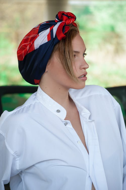 Young woman in stylish apparel and bright kerchief with ornament looking away in daytime