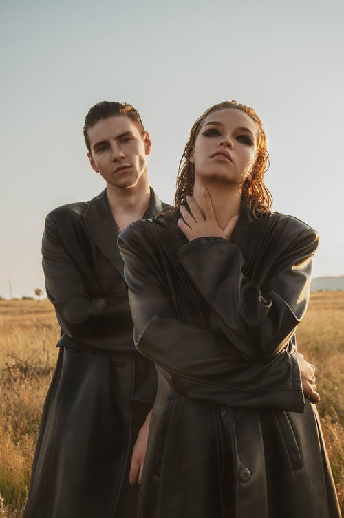 Stylish couple in similar leather cloaks in field