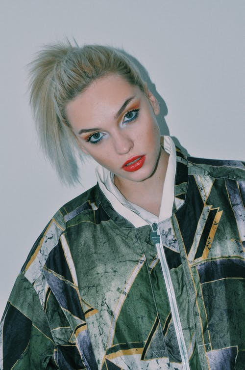 Confident young female model with dyed hair and bright makeup in trendy jacket standing against white background and looking at camera