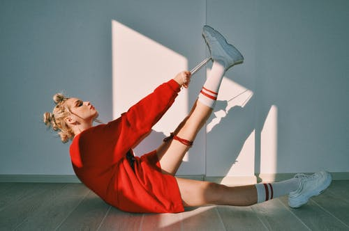 Side view full body of confident female teenager in trendy red dress and socks tying laces of sneakers while sitting on wooden floor near white wall in sunlight