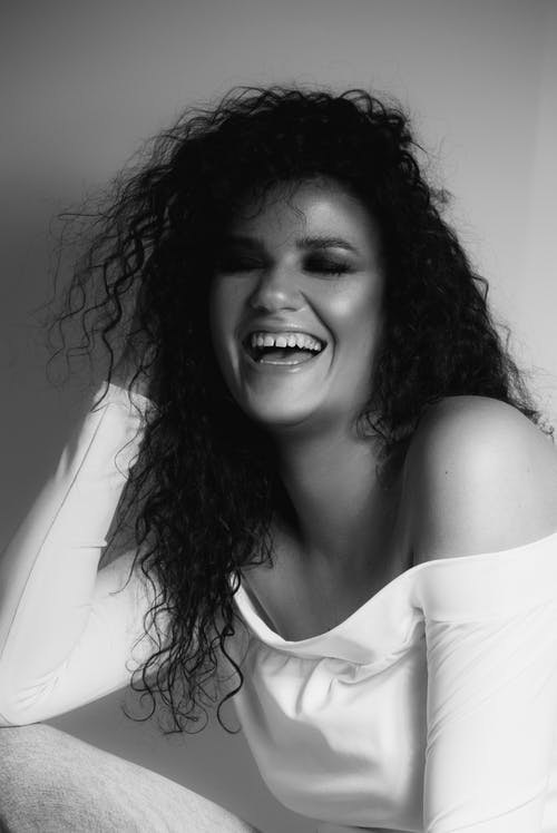 Black and white of cheerful young ethnic female with bare shoulders makeup laughing and touching long curly hair with closed eyes