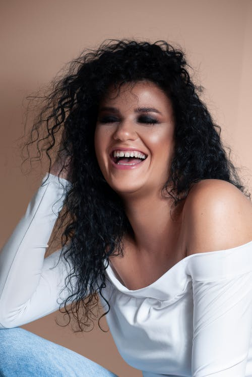 Laughing young ethnic woman with closed eyes sitting in beige studio