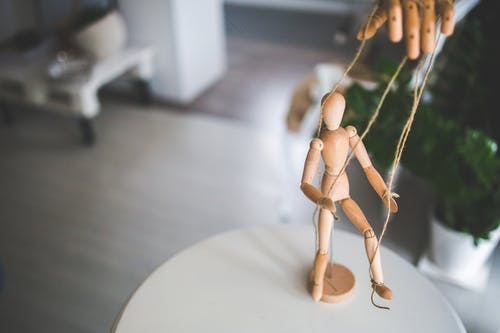 Wooden mannequin as a marionette