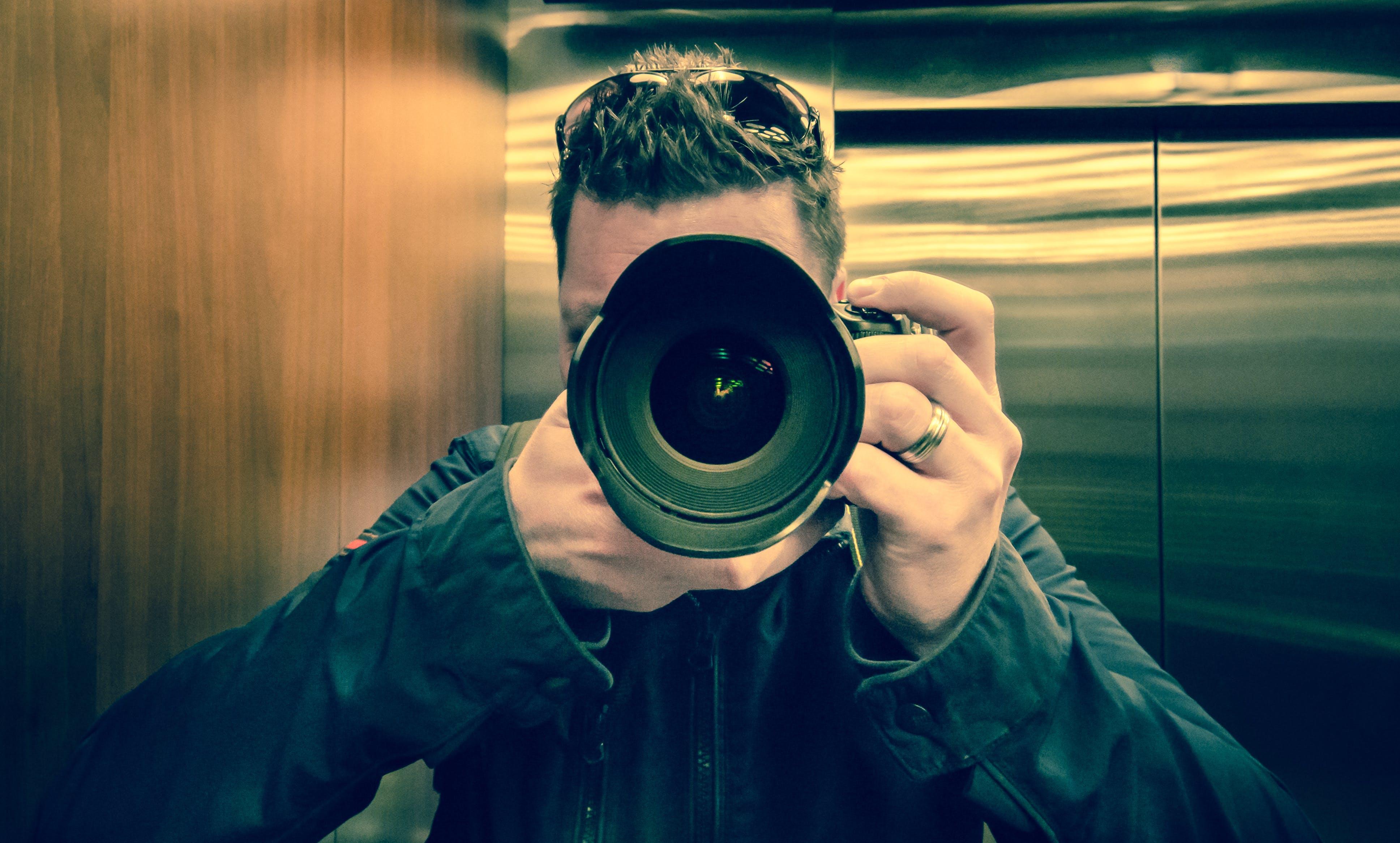 Man in Black Jacket Holding Black Dslr Camera