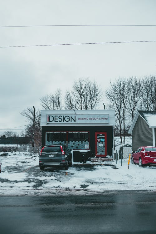 Marketing agency exterior against modern car and SUV parked on snowy pavement under light sky in wintertime