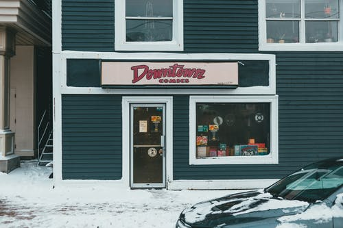 Comic book shop exterior with entrance door and window against snowy pavement and automobile in town