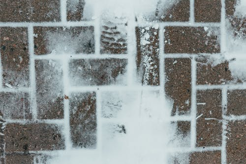 Background of tiled pavement with snow in wintertime