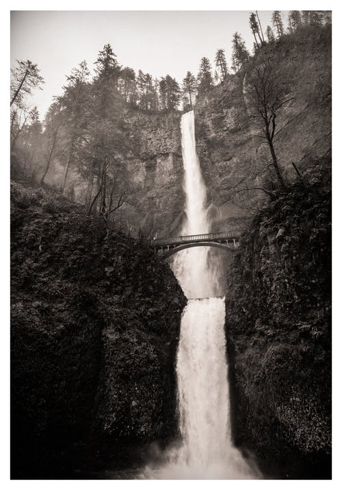 Black and white picturesque scenery of old bridge connecting cliffs covered with lush vegetation against tall fast Multnomah Falls located in Columbia River Gorge
